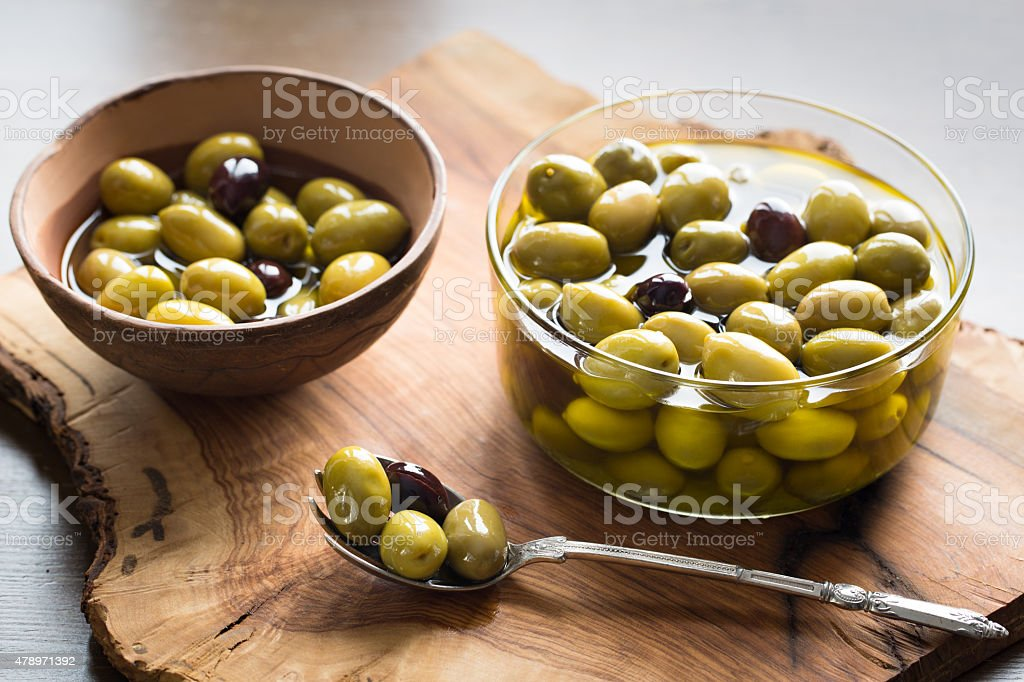 Olives in a bowl on olive wooden board stock photo