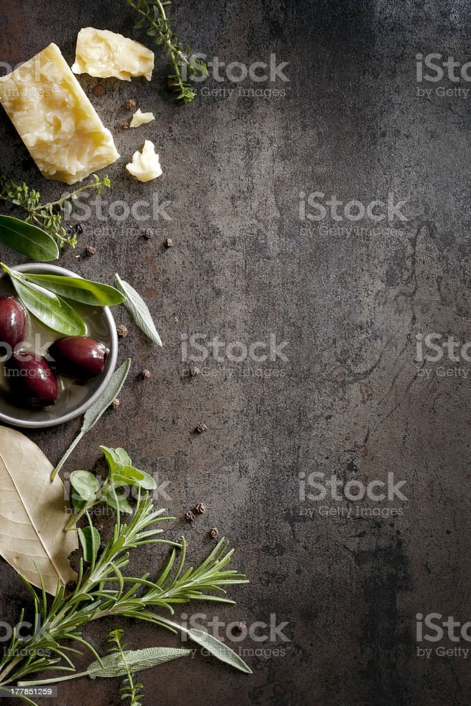 Olives, rosemary, bay leaves and cheese on a wooden surface stock photo