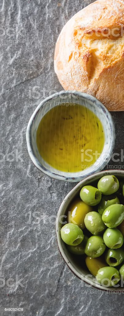 Olivier oil with fresh herbs and bread. Gray background. Italian royalty-free stock photo