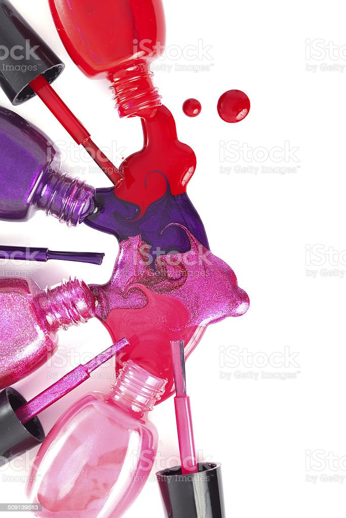 ?olored nail polish  spilling from bottles stock photo