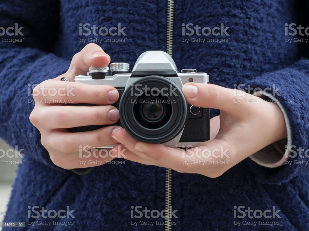 Moscow, Russia - April 23, 2016: Olympus OM-D E-M10 Mark II camera in the hands of 15-year-old girl in a blue coat stock photo