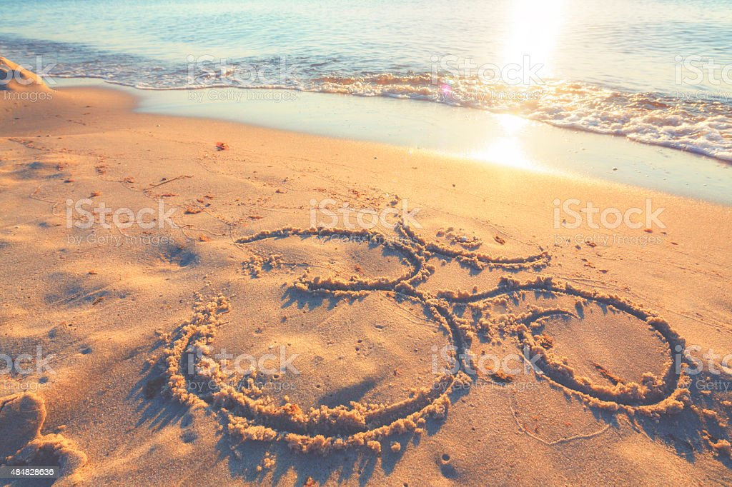 Om symbol in the sand by the ocean stock photo