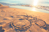 Om symbol in the sand by the ocean