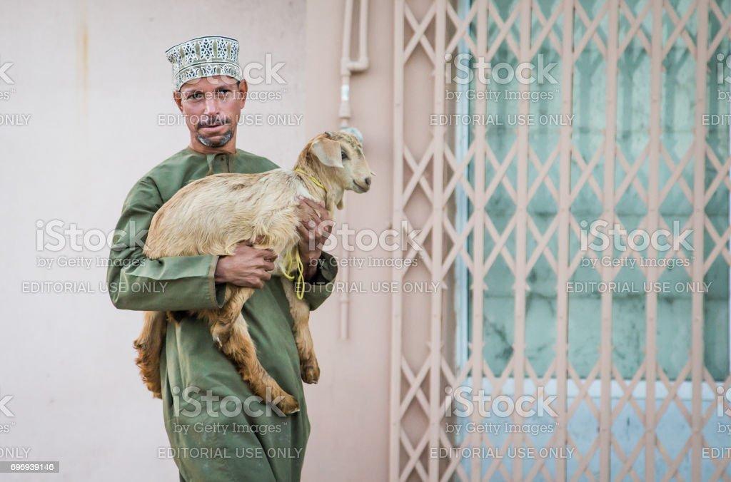 omani man taking a goat to a market stock photo