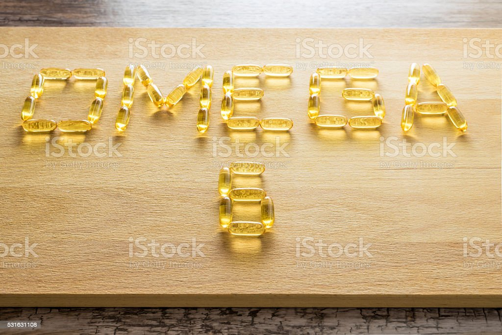 Omega 3-6-9 fish oil yellow softgels drawing omega 6 letters stock photo