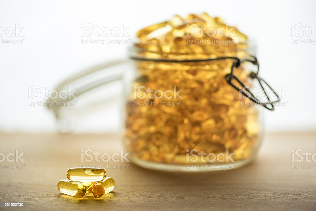 Omega 3-6-9 fish oil yellow softgels into airtight glass jar stock photo
