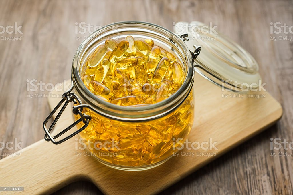 Omega 3-6-9 fish oil yellow softgels on wooden board stock photo