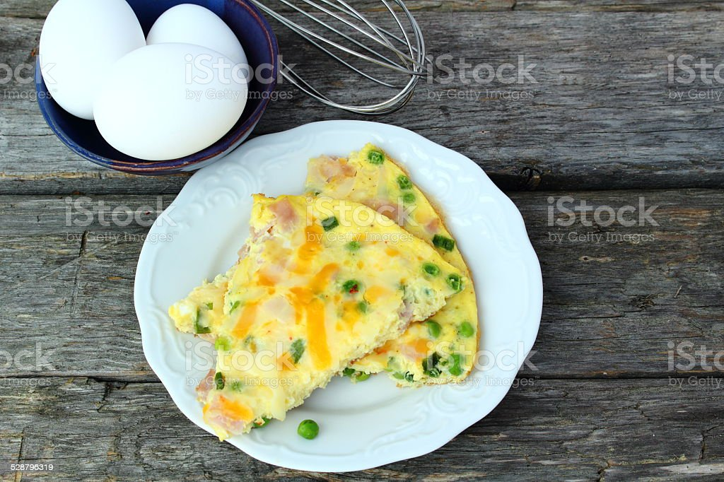 Omelet with ham, cheese and peas stock photo