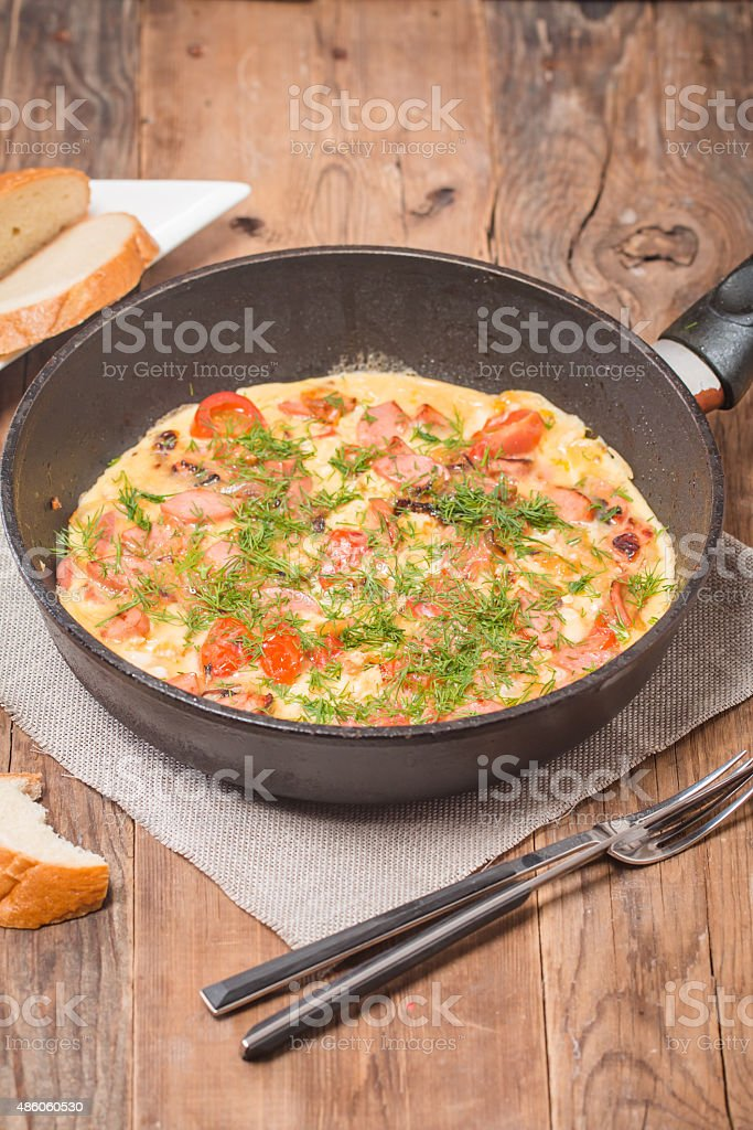 Omelette with sausage, onion, herbs and tomatoes stock photo