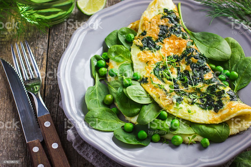 omelette with spinach and green peas stock photo