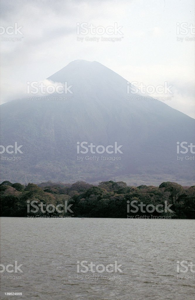 Ominous cone of a volcano over lake stock photo