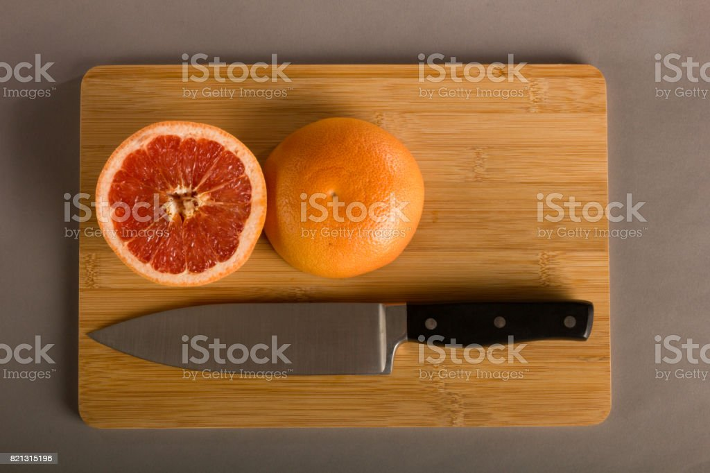 Ominous image of Chef's Knife on Cutting Board with Pink Grapefruit stock photo