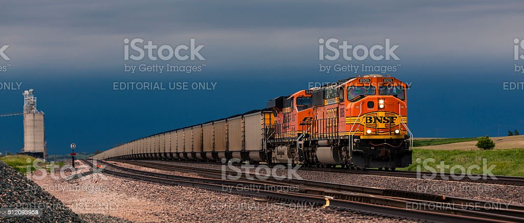 Ominous signs for coal future: loaded train in storm stock photo