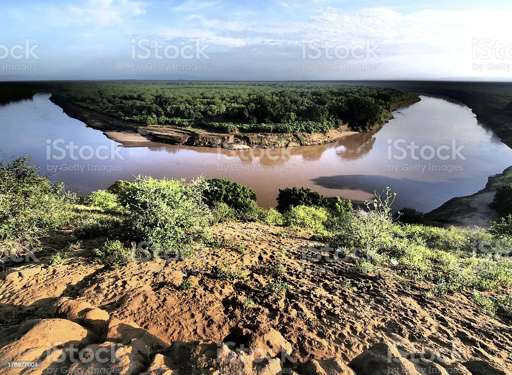 Omo River surrounded by lush green fields on either side. stock photo