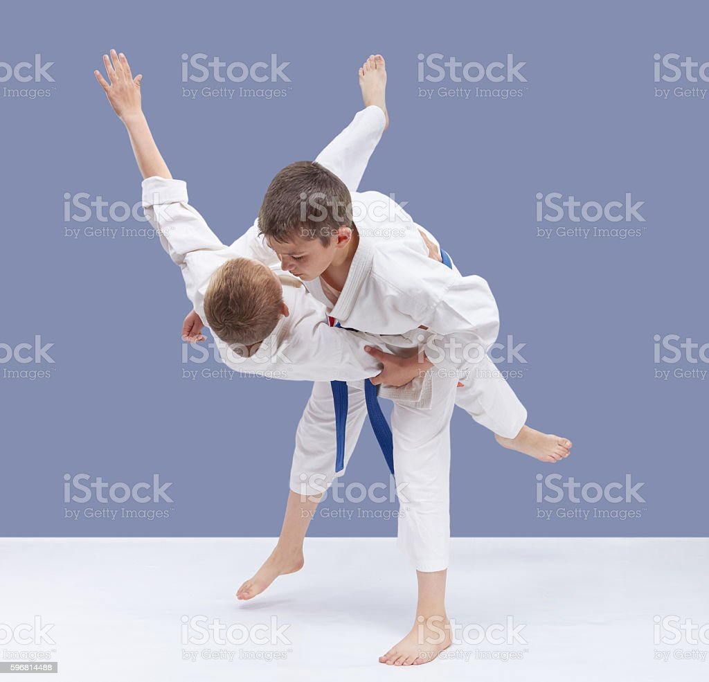 On a gray background boys are trained high throw stock photo