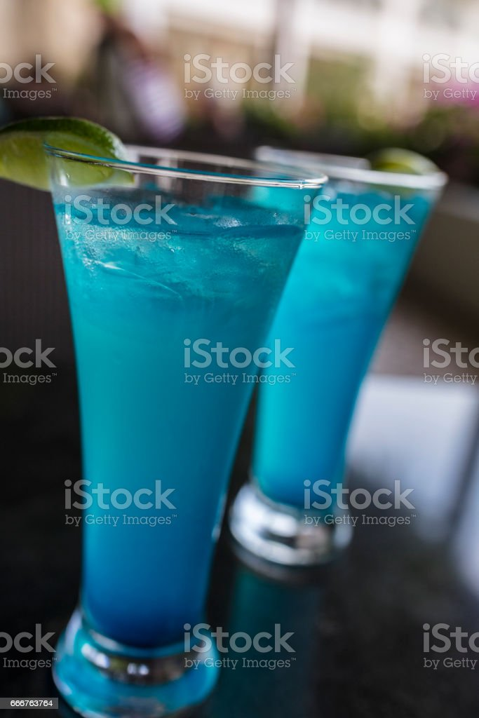 On a Panama City terrace, two refreshing Blue hurricane cocktails made with rum, Curacao, orange and pineapple juices with a lime wedge and lots of ice cubes. stock photo