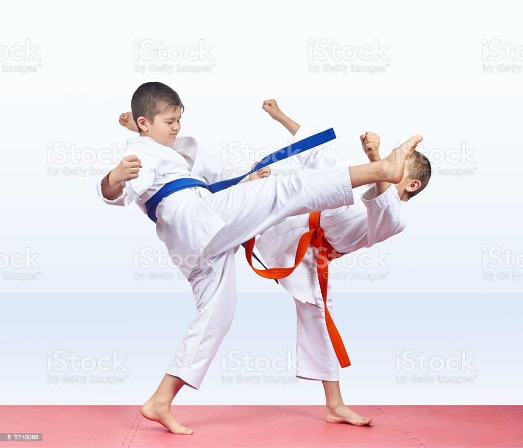 On a red mats children boys are beating kick legs stock photo