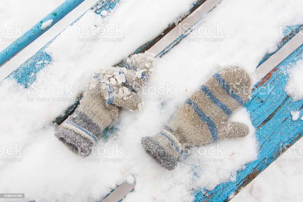 On a snow-covered bench are children mittens forgotten child stock photo