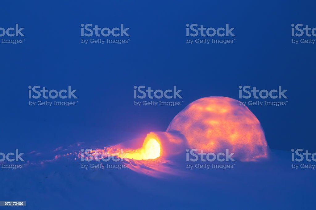 On a snowy meadow is the igloo form which shines the light of candles on a cold winter day. stock photo