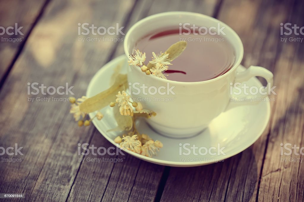 On a wooden table a cup of tea with lime flowers. stock photo