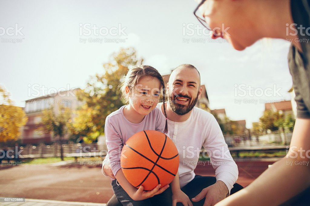 Young family on an outdoors basketball field, playing the game and...