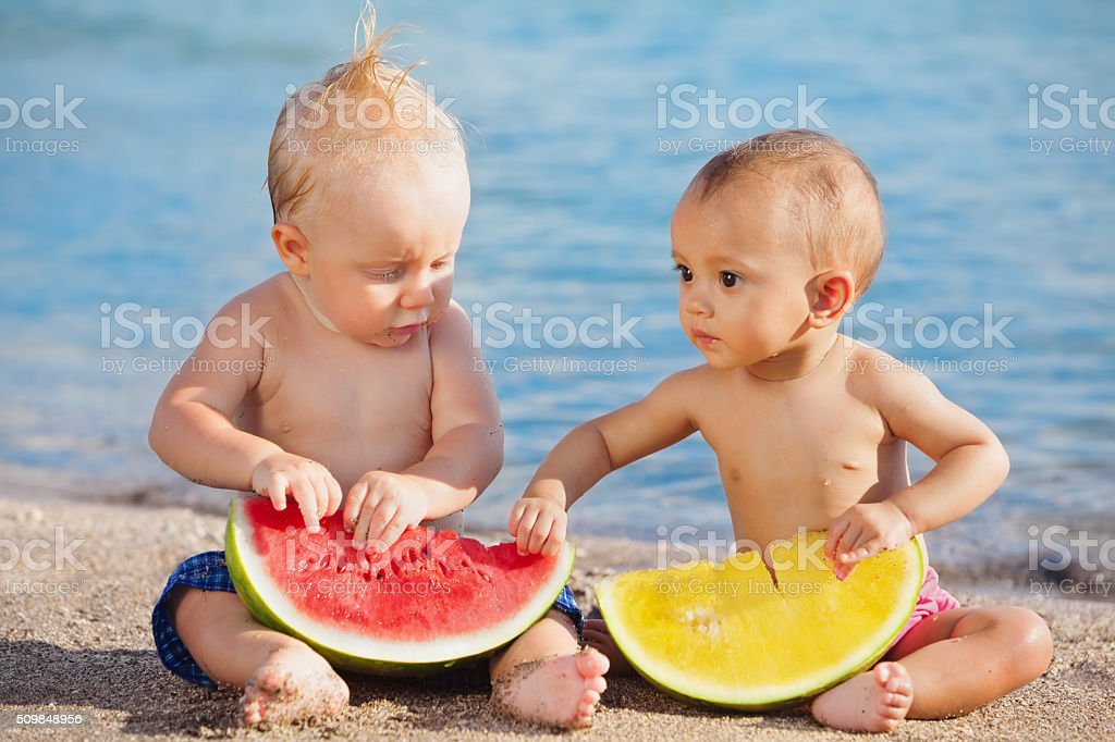 On beach asian and caucasian babies eat fruits fresh watermelons stock photo