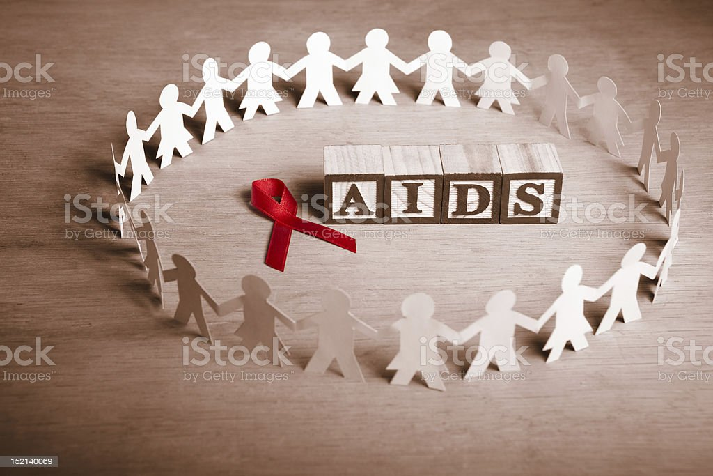 AIDS on building blocks surrounded by cutouts of people stock photo