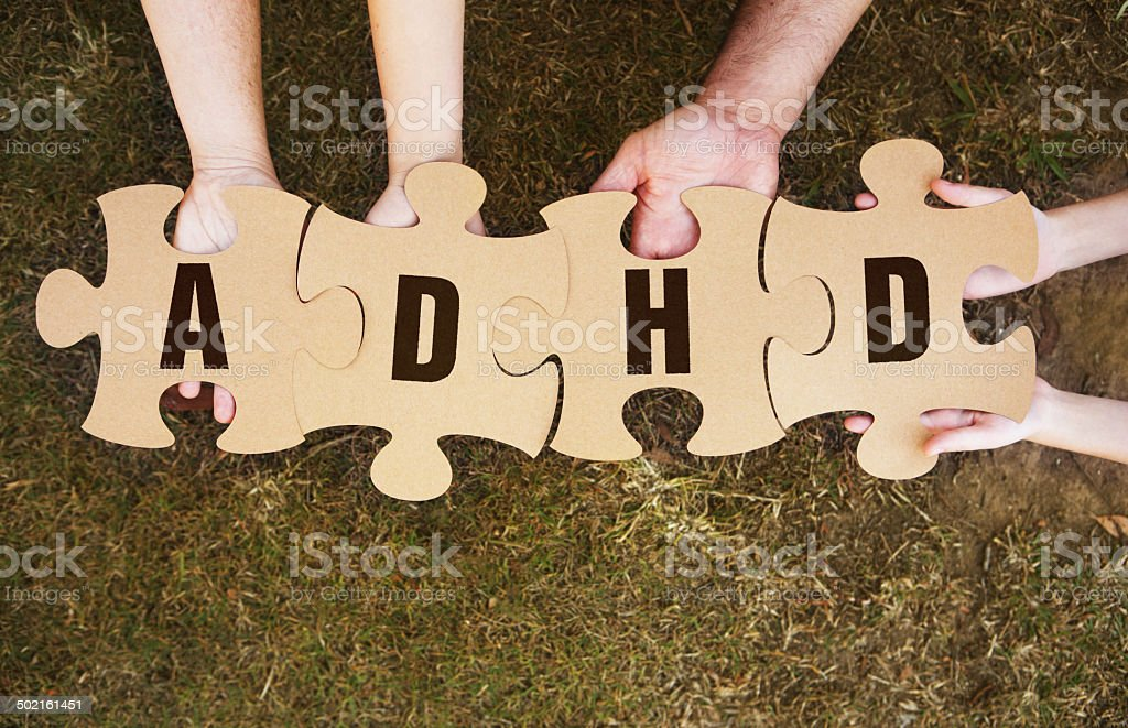 ADHD on Cardboard Jigsaw Puzzle Pieces in Hands stock photo