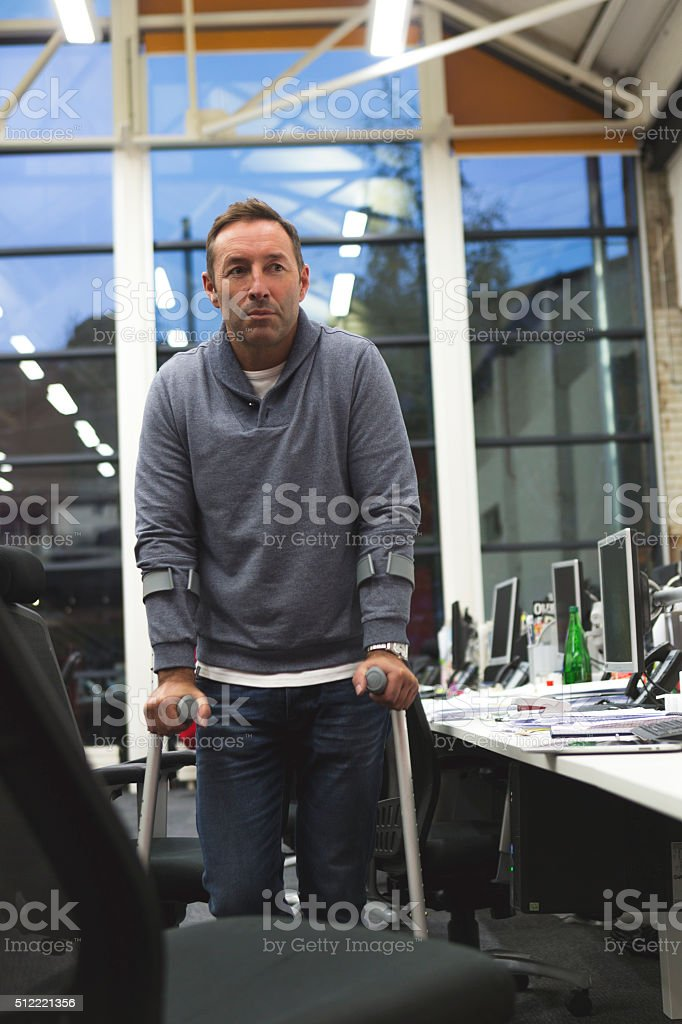 On Crutches in the Office stock photo