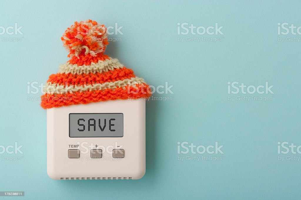 SAVE on digital room thermostat wearing wooly hat stock photo