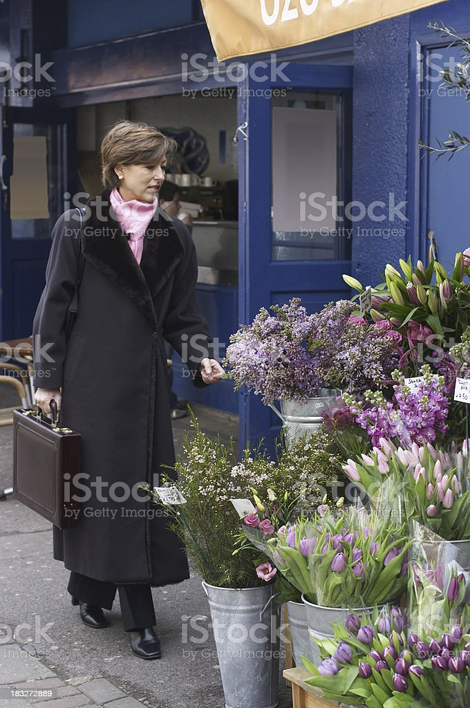 Business lady pauses at flower stall stock photo