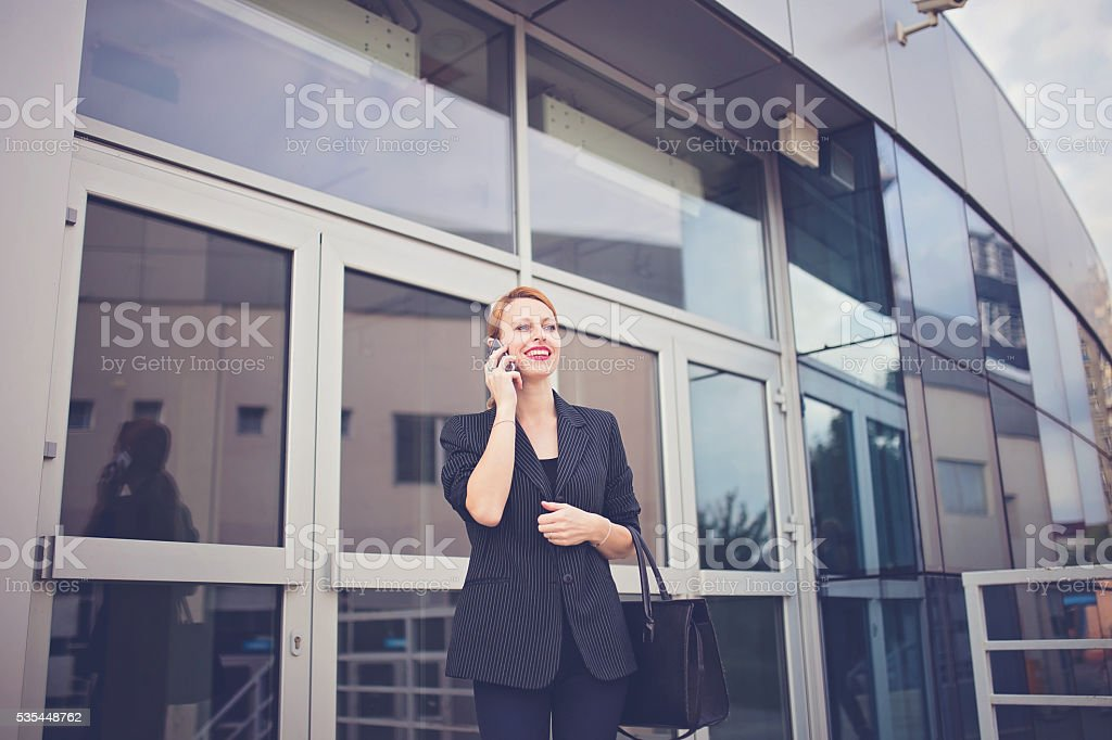 On mobile in front of firm stock photo