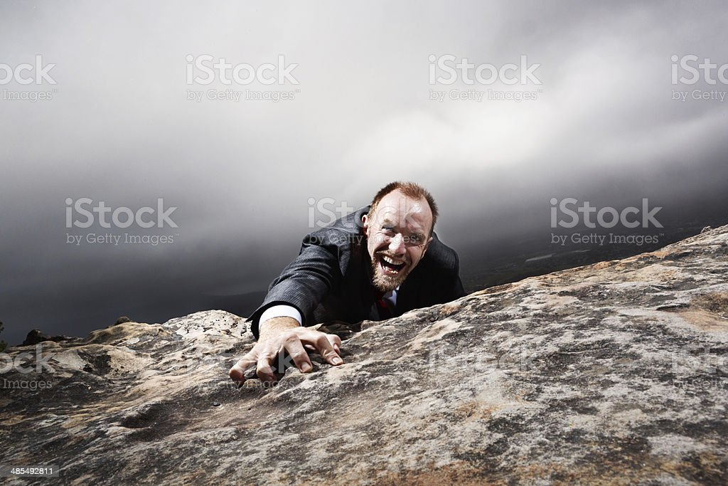 On the edge! Businessman climbing onto mountaintop or slipping off! stock photo