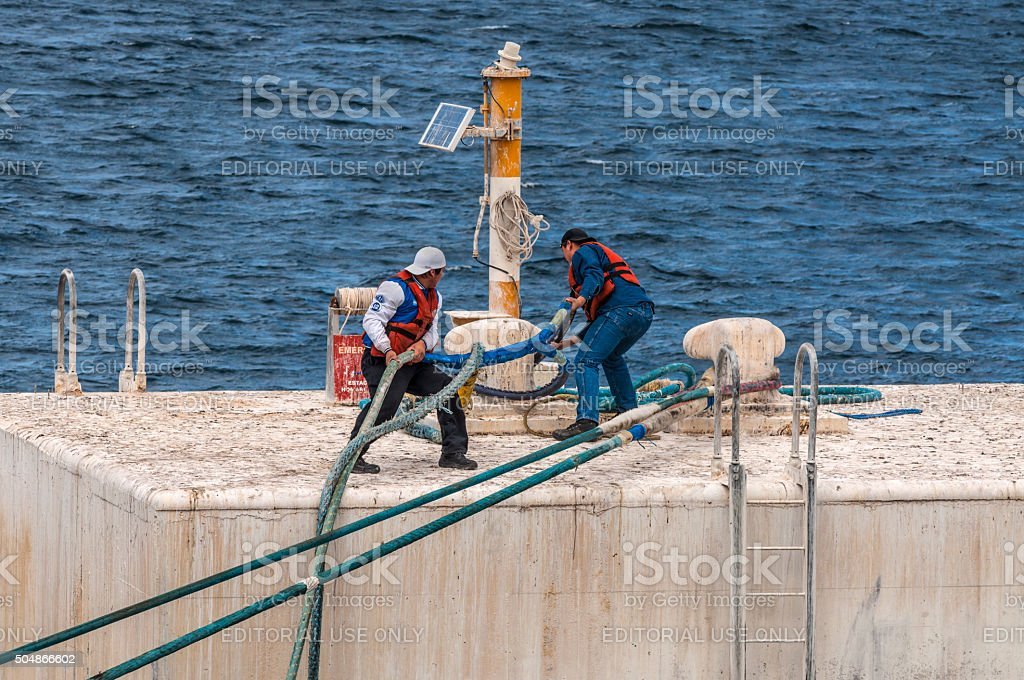 On the mooring platform a workers casts off mooring cable stock photo