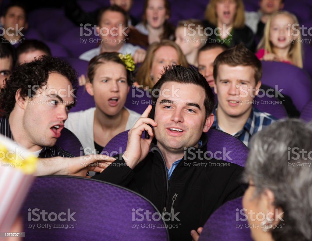 On the Phone in a Movie Theater stock photo