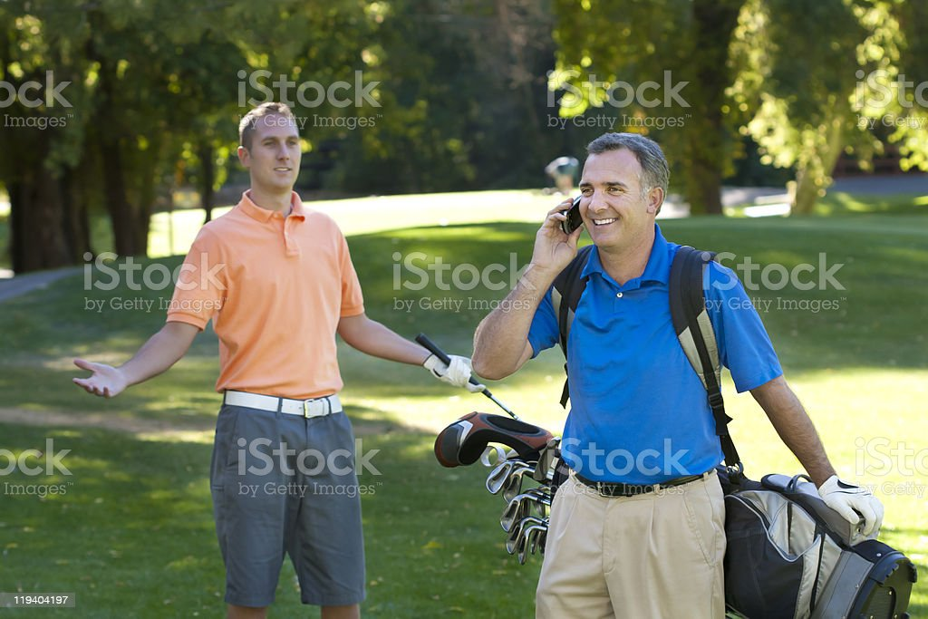 On the phone while golfing stock photo