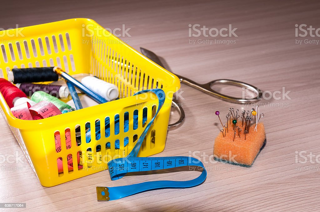 On the table is a basket of tools for sewing stock photo