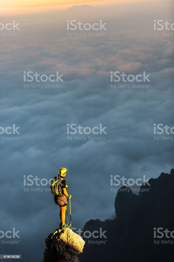 On top of a mountain spire with clouds sea stock photo