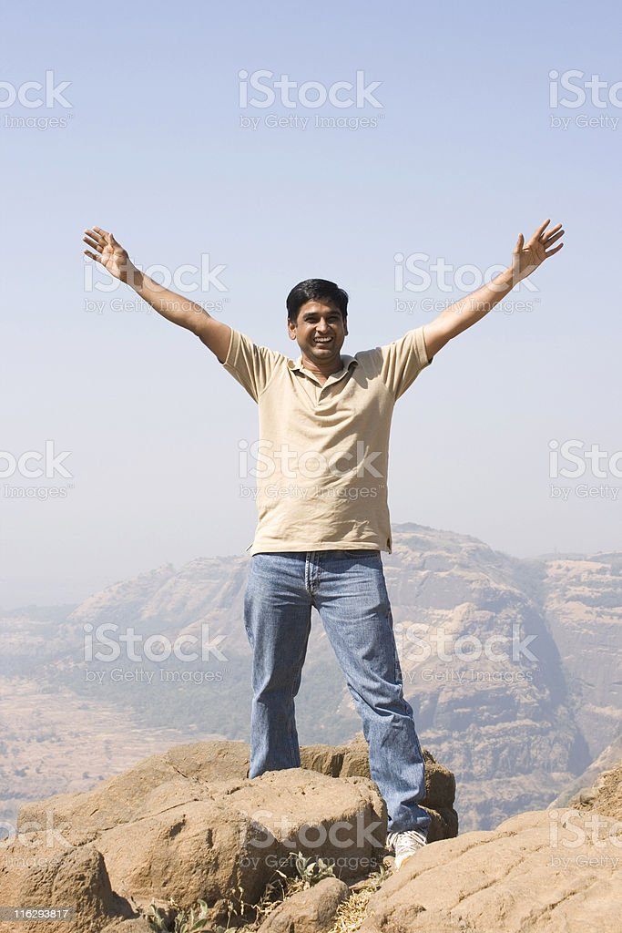 On top of the World Excited Indian male hands up royalty-free stock photo