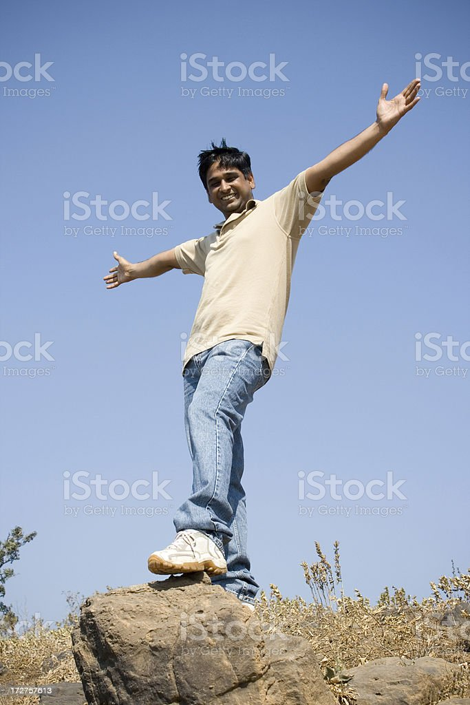 On top of world Happy India male standing at rock royalty-free stock photo