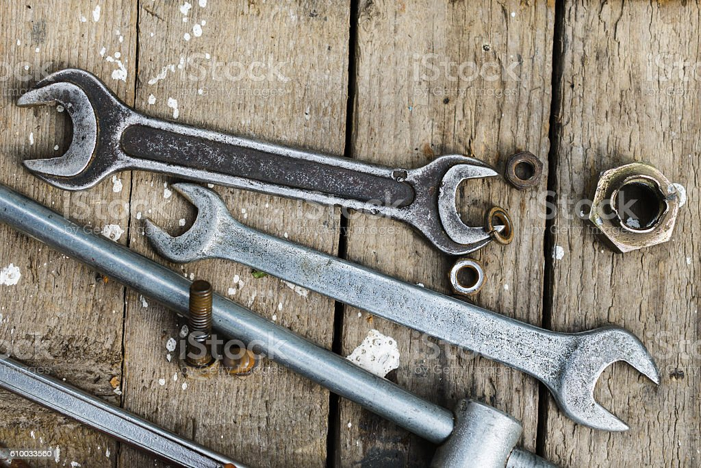 On weathered old wooden surface lie the , oily wrenches. stock photo