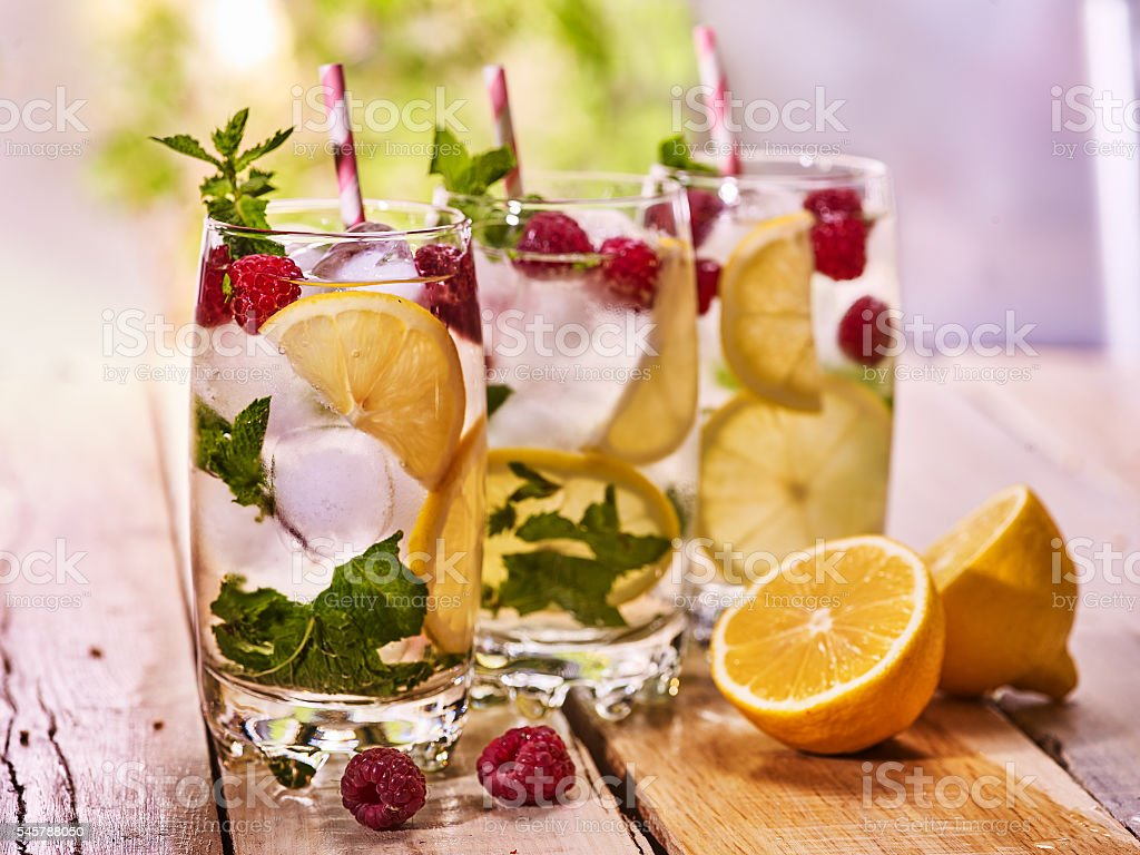 On wooden boards is glass with ice cubes and berries. stock photo