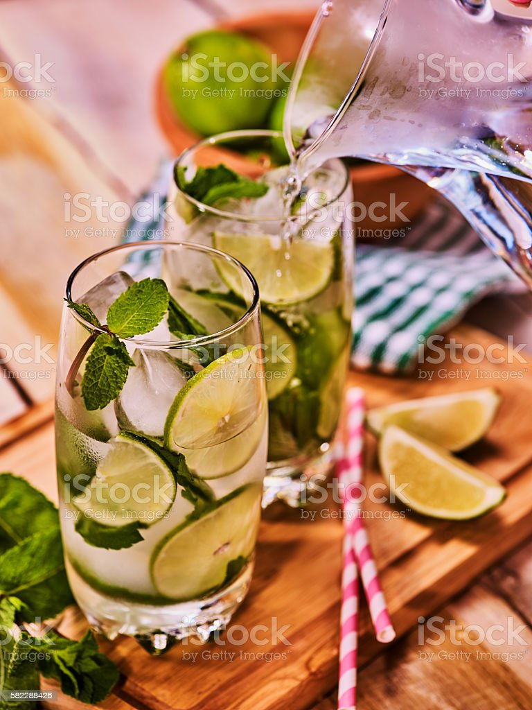 On wooden table jug and glasses with transparent drink. stock photo