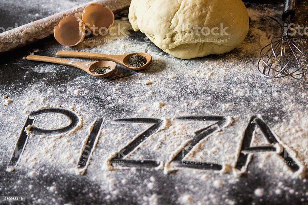 On written flour pasta. Broken egg. Spilling pasta. Top view. stock photo