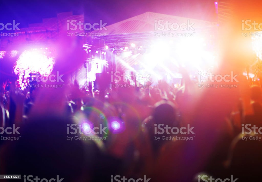Silhouettes of concert crowd in front of bright stage lights. Night...