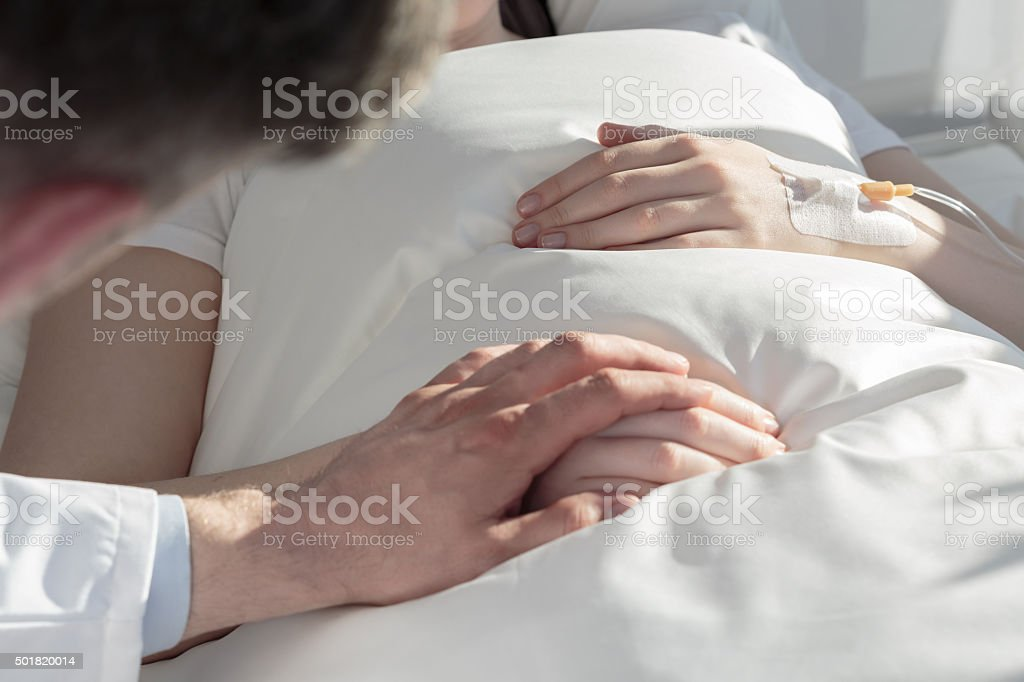 Oncologist holding hand of girl stock photo