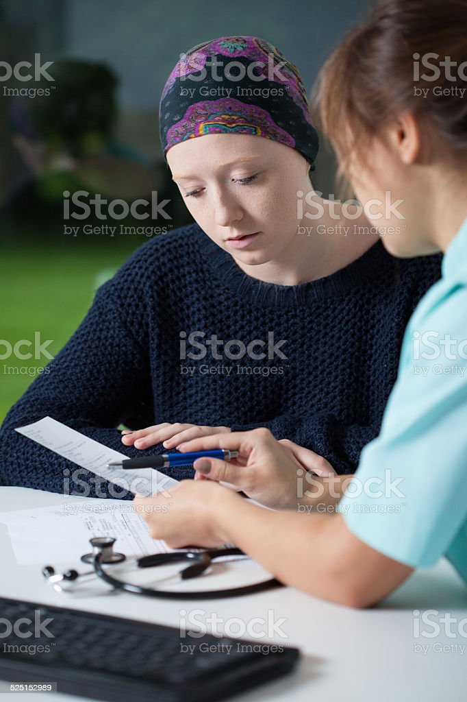 Oncologist talking with young woman stock photo