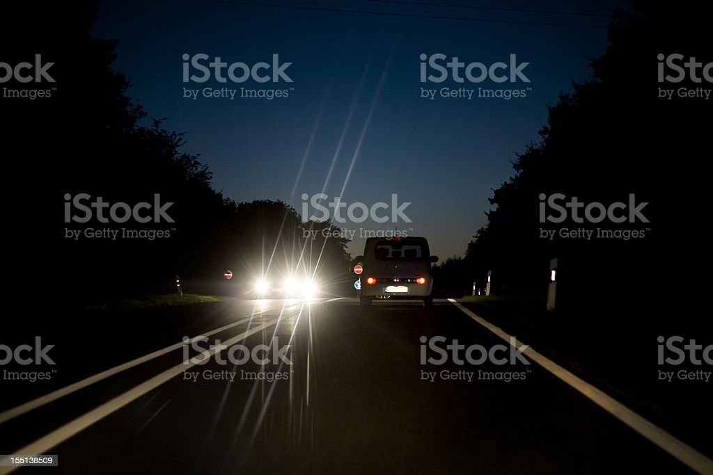 Oncoming traffic on countryroad at dusk stock photo