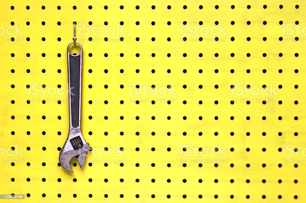 One adjustable wrench hangs from a hook on yellow pegboard stock photo