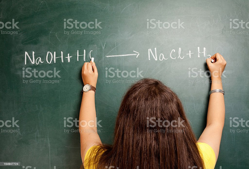 One Ambidextrous Indian Female writing Chemical Equation on Greenboard stock photo
